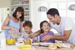 Familia que hace el desayuno en cocina junto Fotografía de archivo