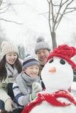 Familia que hace el muñeco de nieve en un parque en invierno imagen de archivo