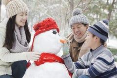 Familia que hace el muñeco de nieve en un parque en invierno fotografía de archivo libre de regalías