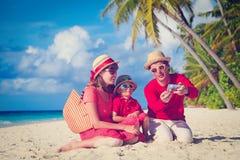 Familia que hace la foto del uno mismo en la playa usando el teléfono Imagen de archivo libre de regalías