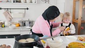 Familia que hace las crepes Una mujer mayor que limpia a las niñas articula de la pasta almacen de video