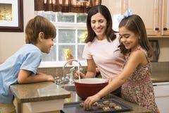 Familia que hace las galletas. Fotografía de archivo