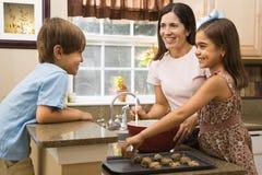 Familia que hace las galletas. imagen de archivo