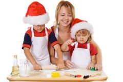 Familia que hace las galletas en el tiempo de la Navidad Fotografía de archivo