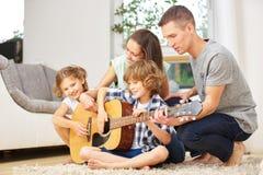 Familia que hace música con la guitarra Foto de archivo libre de regalías