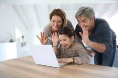 Familia que hace una llamada video en el ordenador portátil imagen de archivo