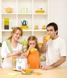 Familia que hace y que bebe el zumo de fruta fresca Imagenes de archivo
