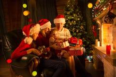 Familia que intercambia los regalos delante de la chimenea en el árbol de navidad Imágenes de archivo libres de regalías