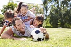 Familia que juega al fútbol en jardín junto Imagen de archivo