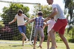 Familia que juega al fútbol en jardín junto fotos de archivo