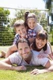 Familia que juega al fútbol en jardín junto imágenes de archivo libres de regalías