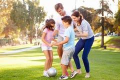Familia que juega al fútbol en parque junto Imagen de archivo