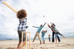 Familia que juega al grillo en la playa Foto de archivo libre de regalías