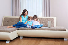 Familia que juega al videojuego en el teléfono elegante Imagen de archivo libre de regalías