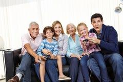 Familia que juega al videojuego junto en Smart TV Imagen de archivo libre de regalías