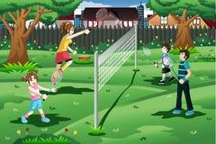 Familia que juega a bádminton en el patio trasero Imagen de archivo