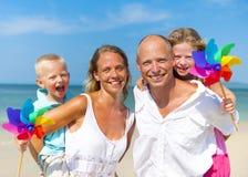 Familia que juega con el molino de viento en la playa Imagenes de archivo