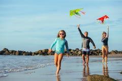 Familia que juega con la cometa en vacaciones de verano Imagenes de archivo