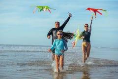 Familia que juega con la cometa en vacaciones de verano Fotos de archivo libres de regalías