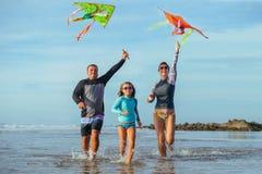Familia que juega con la cometa en vacaciones de verano Imagen de archivo