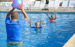 Familia que juega con la pelota de playa colorida en piscina Imagen de archivo libre de regalías