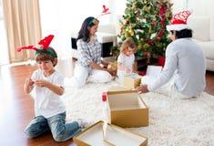 Familia que juega con los regalos de la Navidad en el país Foto de archivo libre de regalías