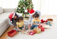 Familia que juega con los regalos de Navidad en el país Fotos de archivo