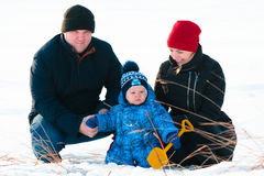 Familia que juega con su niño en la nieve en el parque Foto de archivo