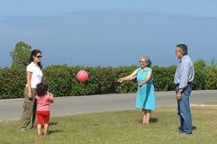 Familia que juega con una bola imagen de archivo libre de regalías