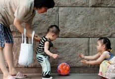 Familia que juega con una bola Fotografía de archivo libre de regalías