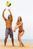 Familia que juega con una bola en la playa Imagen de archivo libre de regalías