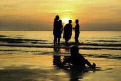 Familia que juega el agua en la salida del sol Imagen de archivo