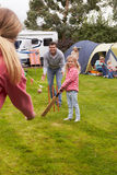 Familia que juega el partido del grillo en acampada foto de archivo