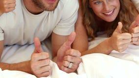 Familia que juega en cama con los pulgares para arriba almacen de video