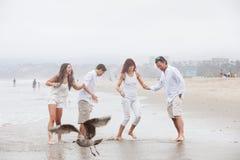 Familia que juega en el agua en la playa Foto de archivo