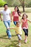 Familia que juega en el campo verde Fotos de archivo libres de regalías