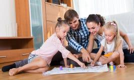 Familia que juega en el juego de mesa imagen de archivo