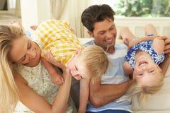 Familia que juega en el sofá en el país Fotografía de archivo libre de regalías