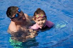 Familia que juega en la piscina Fotos de archivo libres de regalías