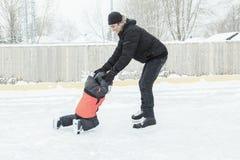 Familia que juega en la pista de patinaje en invierno Foto de archivo