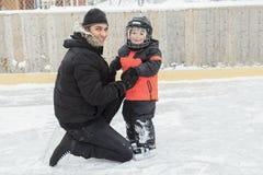 Familia que juega en la pista de patinaje en invierno Fotos de archivo libres de regalías