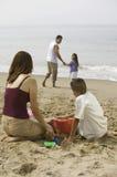 Familia que juega en la playa Imagen de archivo libre de regalías