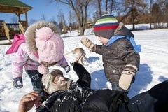 Familia que juega en nieve Imagen de archivo libre de regalías