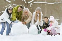 Familia que juega en nieve fresca Imágenes de archivo libres de regalías