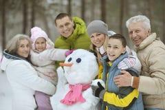 Familia que juega en nieve fresca Fotos de archivo libres de regalías
