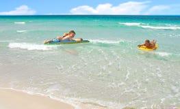 Familia que juega en resaca del océano Imágenes de archivo libres de regalías