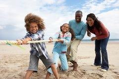 Familia que juega esfuerzo supremo en la playa Foto de archivo