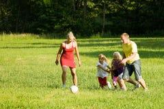 Familia que juega a fútbol Imagen de archivo libre de regalías