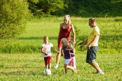 Familia que juega a fútbol Imagenes de archivo