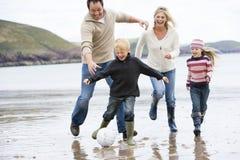 Familia que juega a fútbol en la sonrisa de la playa Fotografía de archivo